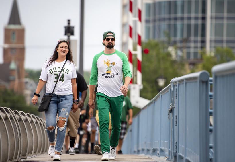 Fans walk across a bridge.