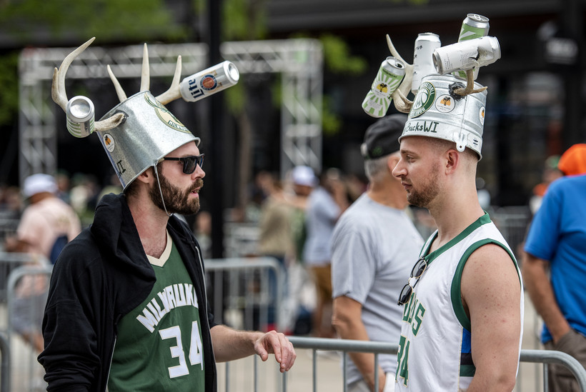 Two fans wear buckets on their heads with antlers and beer cans attached.