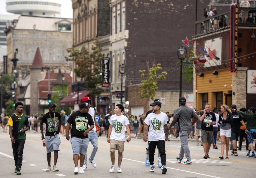 Fans walk in a blocked off street near the Fiserv Forum.