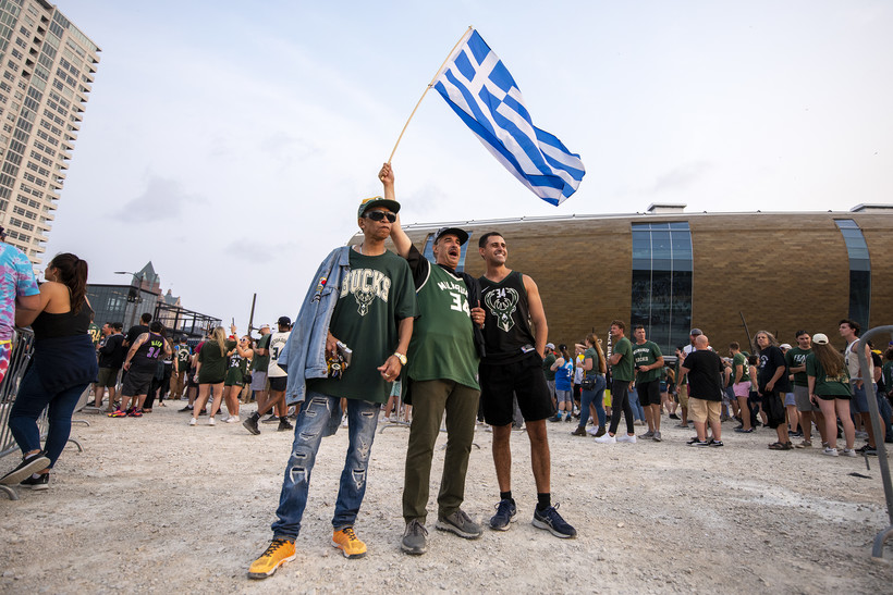 Three men stand together. One waves the blue and white Greek Flag up high.