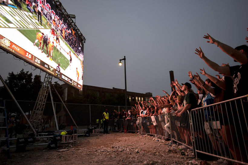 Fans raise their arms to a screen showing the game.