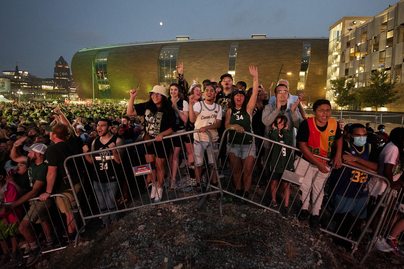 Fans stand on a hill behind barricades.