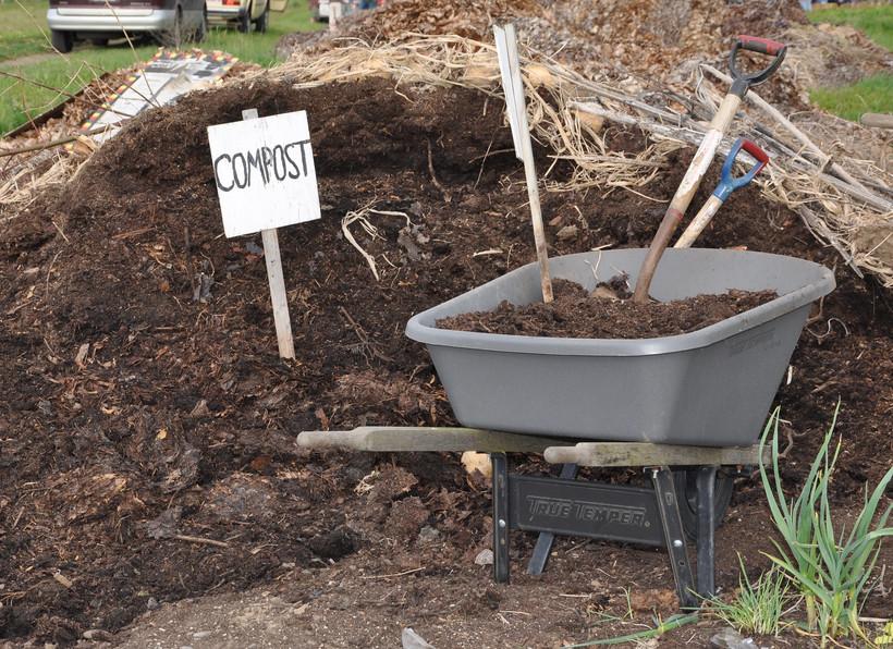 Compost pile with wheelbarrow.