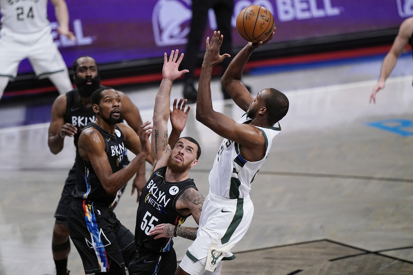 Nets Mike James defends Bucks forward Khris Middleton as he goes up for a layup