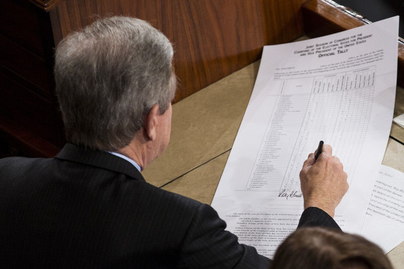 Sen. Roy Blunt, R-Mo., left, signs off on an official tally following a joint session of Congress to count Electoral College