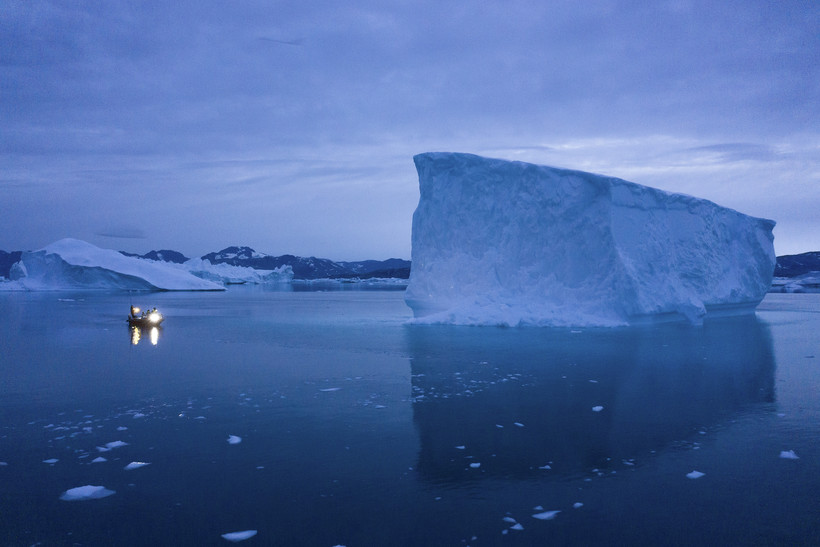 A boat navigates at night next to large icebergs in eastern Greenland.