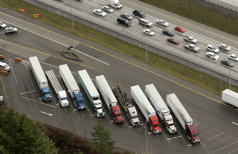Semi trailer trucks fill slots at a weigh station as traffic passes