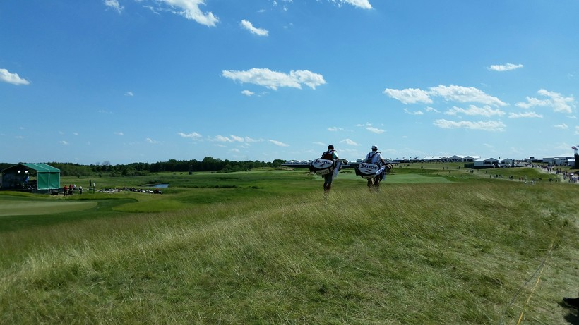 Two caddies carrying golf bags at the U.S. Open.