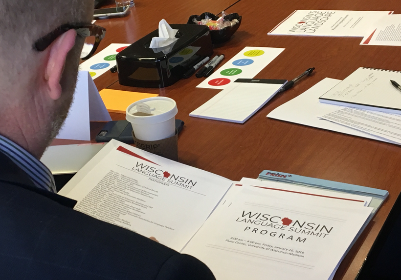 Man looks at folder with documents titled Wisconsin Language Summit Program