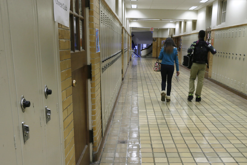 two students walk in a hallway