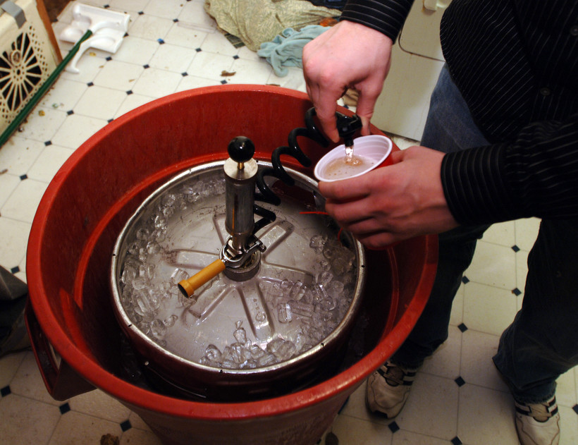 A plastic cup is filled with beer from a keg