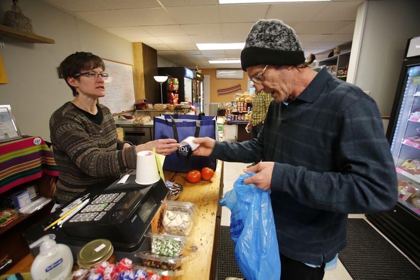 Dianne Shenk, left, helping customer Terry Warby