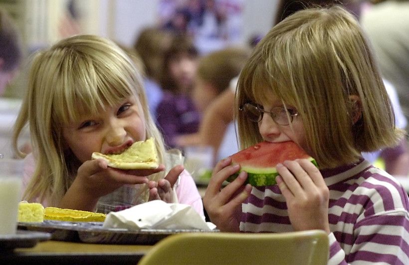 Kayla Reynolds, 6, left, and Kirsten Desorda, 7, eatlunch at school