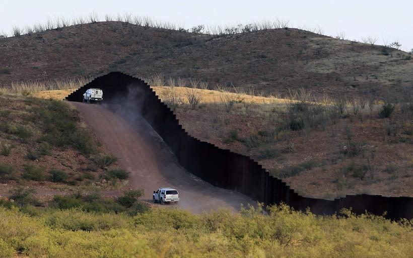 U.S. Border Patrol agents patrol the border fence in Naco, Ariz