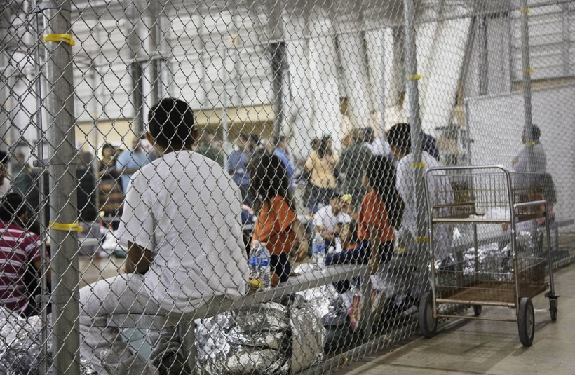 immigrants who've been taken into custody sit in one of the cages at a facility in McAllen, Texas