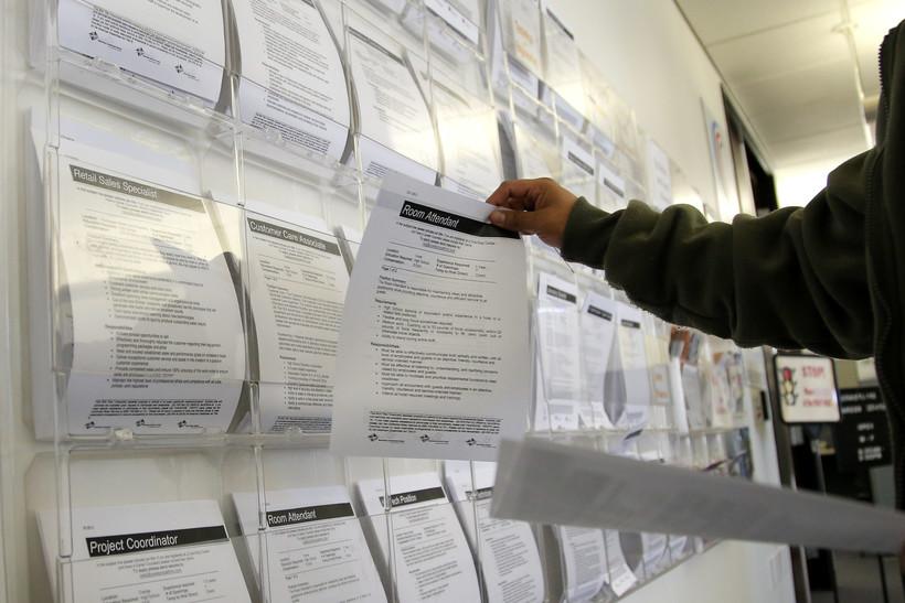 A job seeker grabs a flyer advertising a job