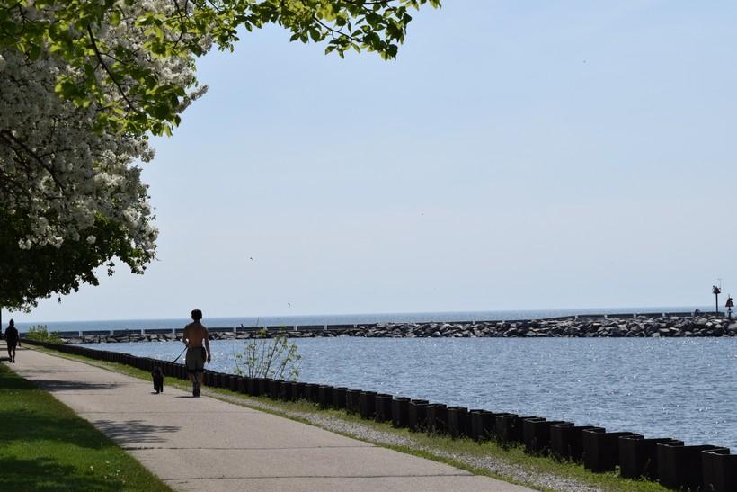 Photo of people strolling on a sidewalk near Lake Michigan