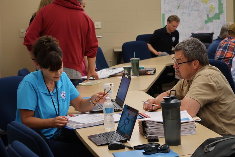 Burnett County Emergency Management Director Jim Tolbert goes over damage estimates with a FEMA representative