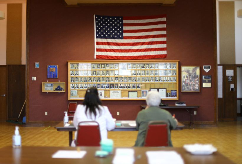 Julie Routhieaux, administrative specialist for the village of Little Chute, Wisconsin, left, and Patti Seeman, an election inspector, help out with voting at the village hall
