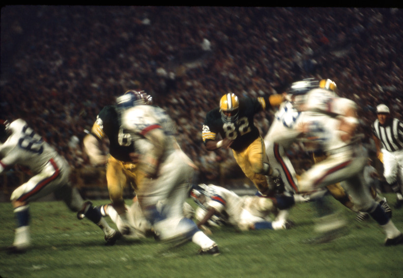 In a blur of excitement Lionel Aldridge (82) and Ray Nitschke (66) push through the Giants offense