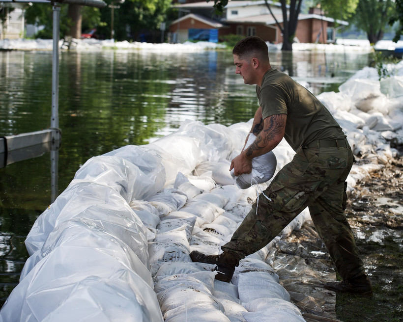 A soldiers assists local citizens in sandbagging efforts after flooding