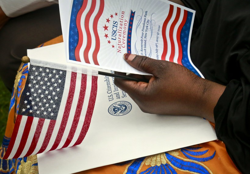 Fatoumata Jangana holds a program and flag during U.S. Citizen and Immigration Services ceremony