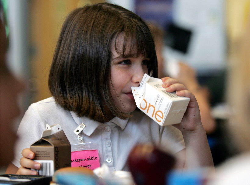 child drinks from containers of one percent milk