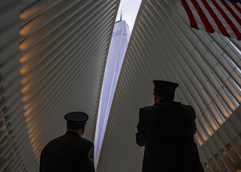 Two members of the New York City fire department look towards One World Trade Center