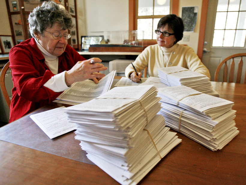 A town clerk and election official check absentee ballots