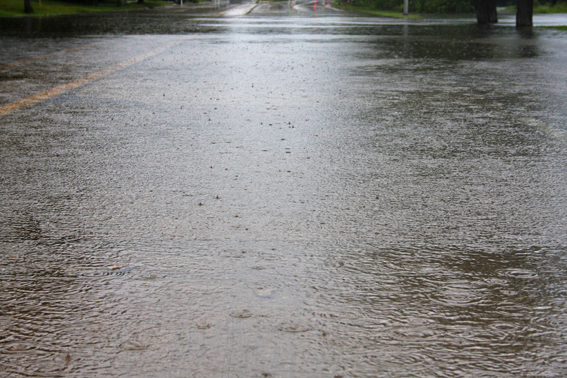 Floodwater spills out of the TenneyPark Lagoon and onto East Johnson Street after heavy rainfall