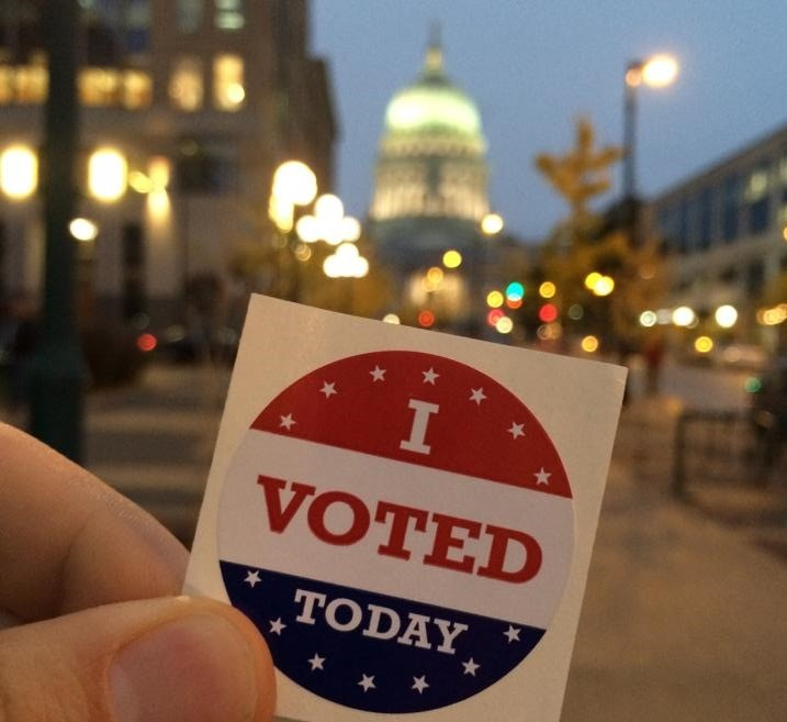 """I Voted Today"" sticker held in front of the Wisconsin state capitol"