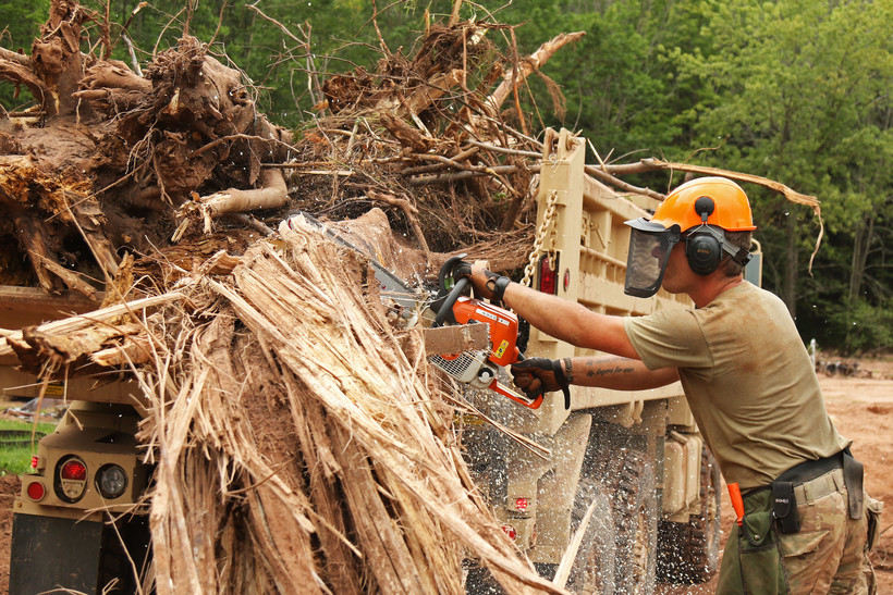 Spc. Justin Meagher operates a chain saw to cut up large debris