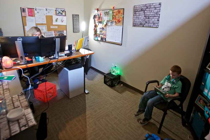 atie Arnold works while her son Rowen Arnold plays educational games on her iPad
