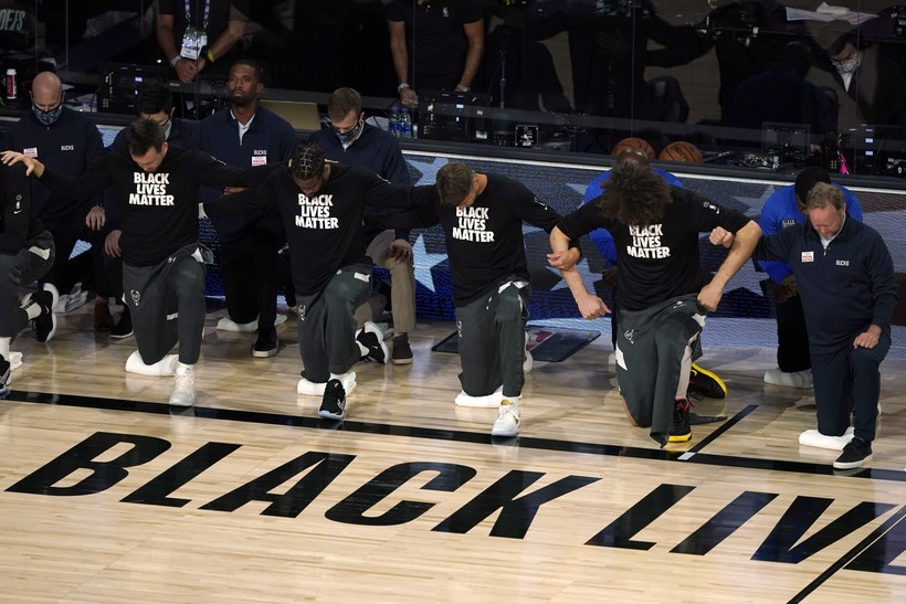 Members of the Milwaukee Bucks join arms as they kneel during the national anthem