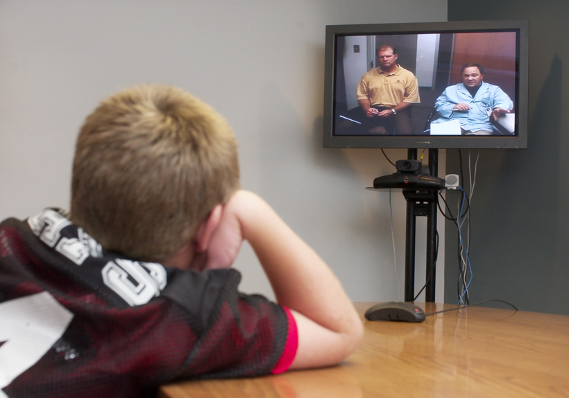 A student talks over video teleconferencing with his doctor and psychologist