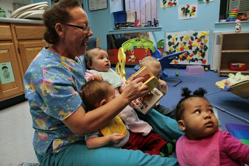 nurse reading to infants