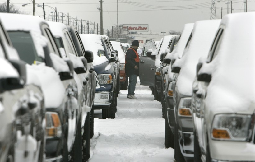 A lot employee looks over Dodge Ram trucks parked in a holding lot in Warren