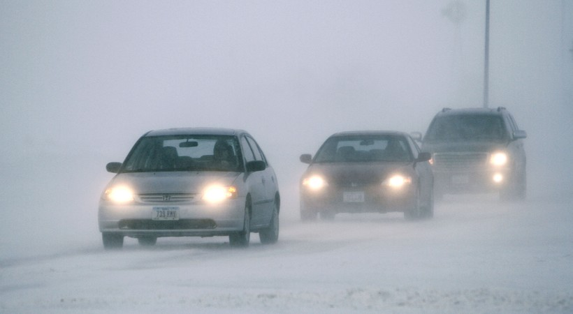 Motorists make there way down a snow-covered road