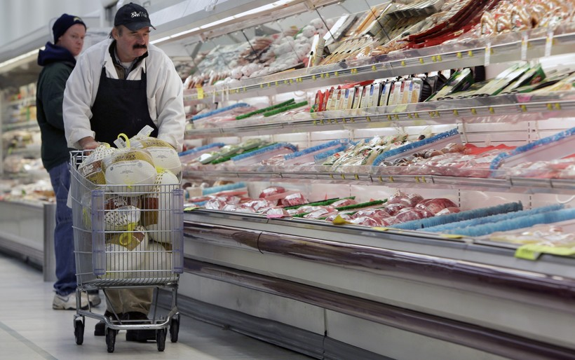 A meat manager, pushes a shopping cart full of turkeys for stocking
