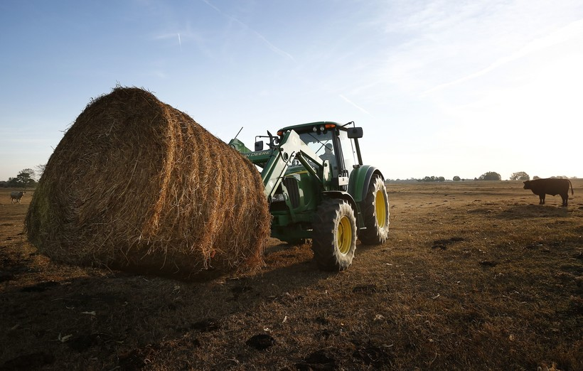 Colton Murdock drives a bale of hay on a tractor