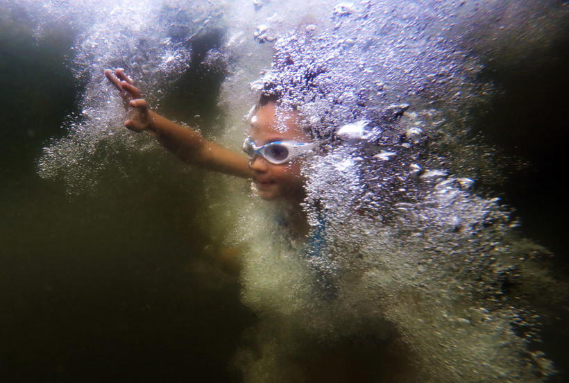 child surfaces through a wall of bubbles after jumping into Lake Wood