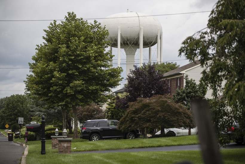 a water tower stands above a residential neighborhood