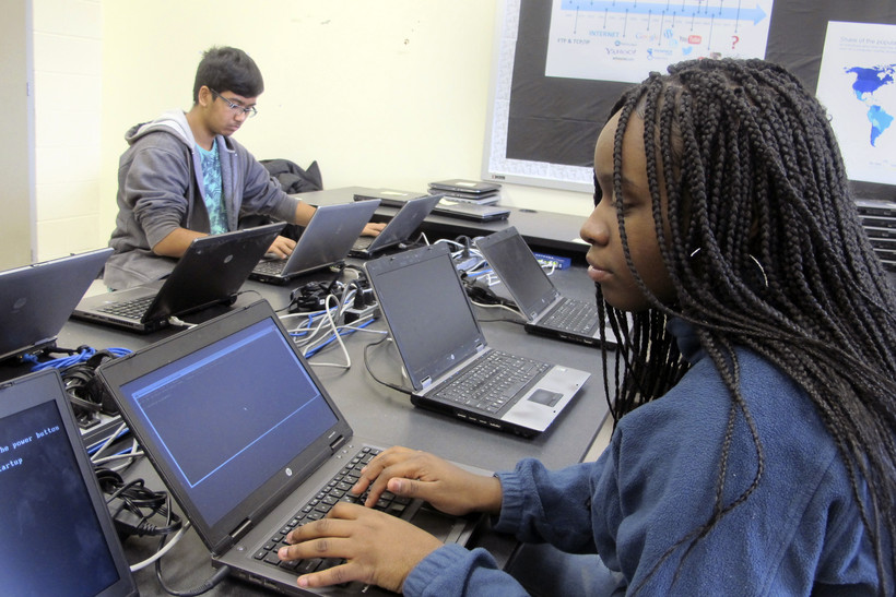 students work on re-imaging laptops in a school computer lab