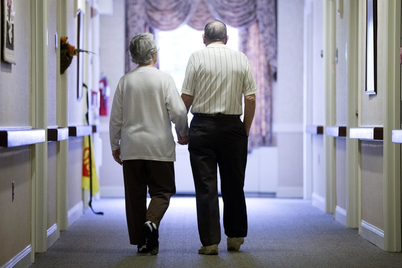 elderly couple walks down a hall of a nursing home