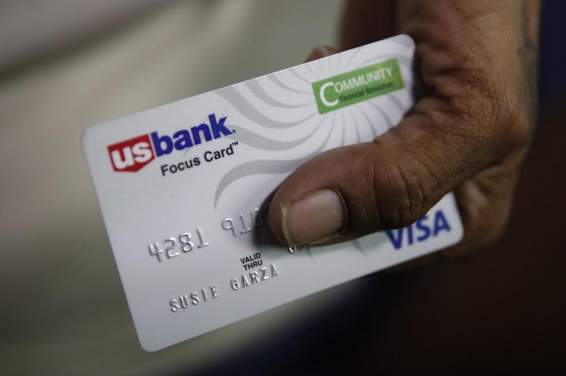 Susie Garza displays her city provided debit card