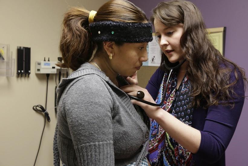 medical resident Stephanie Place examines Maria Cazho