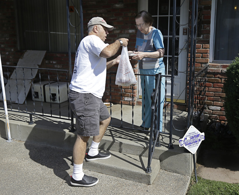 Bob Gill, a volunteer with Meals on Wheels, delivers lunch to Thelma Pense