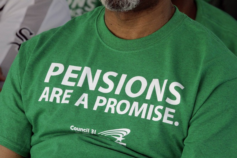 American Federation of State County and Municipal Employees union members wear a protest message on pensions