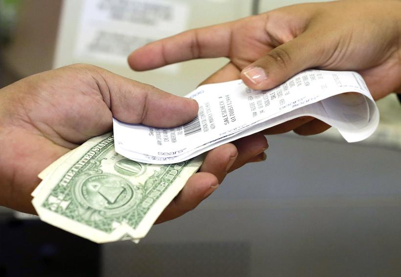 Acashier hands a customer his receipt