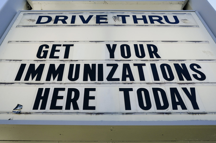 A sign with text about drive-thru vaccinations